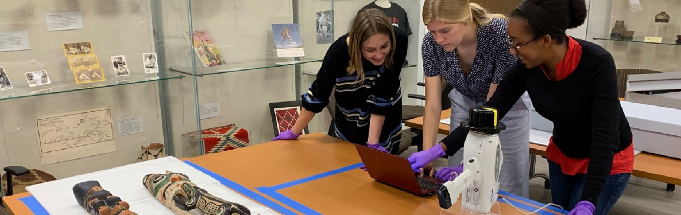 Three people use an XRF to study artifacts