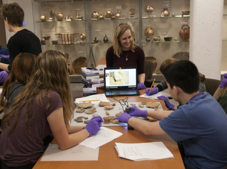 Graduate student working with high school students and ceramic sherds