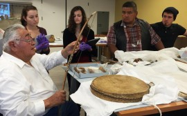 Tribal cultural experts Walter Lara, Yurok Tribe (seated left) and Glen Moore and Chance Carpenter ('15), Hoopa Valley Tribe (standing right) explore late 19th-century collections from northern California with students (2015).