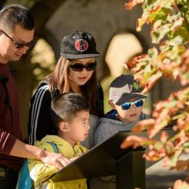 The Xiong family from Shenzhen, China, interacts with one of the new interpretive kiosks designed to share the story of Stanford's transformational impact over 125 years.