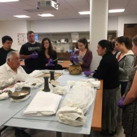 Walter Lara (Yurok Tribe), sitting left, and Melodie George-Moore (Hoopa Valley Tribe), standing right leaning on the table, discuss Daggett Collection items with students.