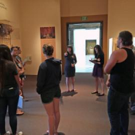 Museum Cultures class members with museum staff discussing exhibit design in the Africa gallery at the Cantor Center, Stanford University.